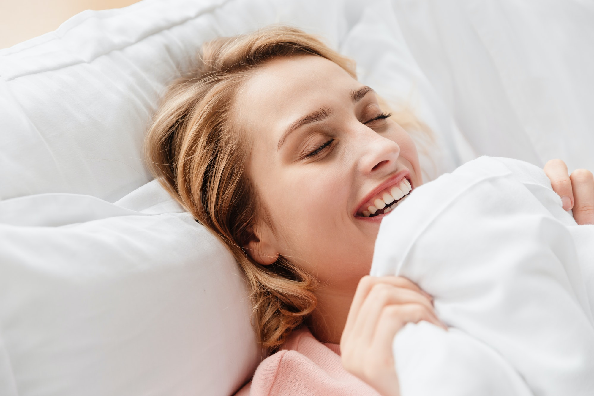 Optimistic young woman at home lies in bed under blanket.